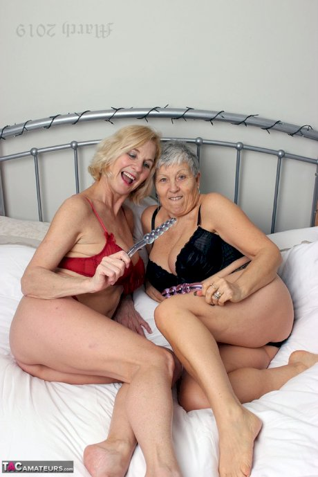 Short haired granny Savana and her lesbian girlfriend toy pussies on a bed