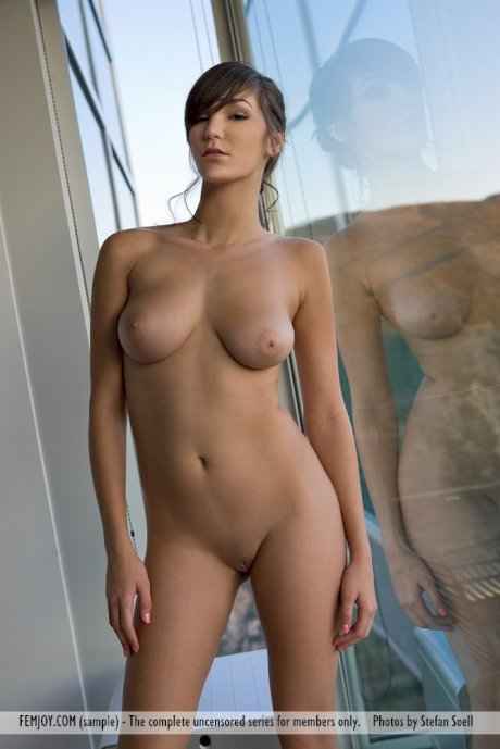 Long legged model Holly M flaunts her nice tits in front of windows
