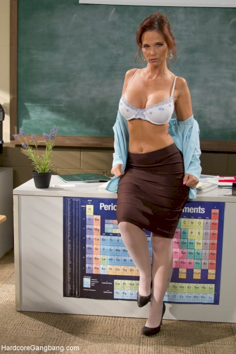 Sexy MILF teacher Syren De Mere undresses to show her big tits in class
