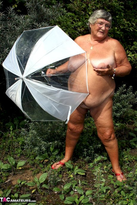 Obese oma Grandma Libby holds an umbrella while posing naked by fir trees