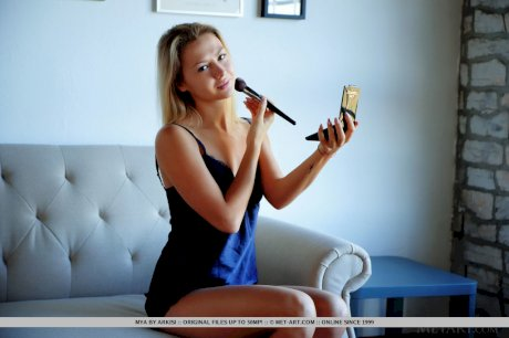 Young solo girl Mya fixes her makeup prior to a nude modelling gig
