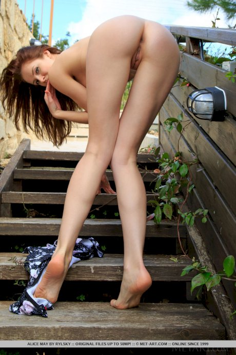 Young redhead Alice May showcases her tight slit on wooden stairs outdoors