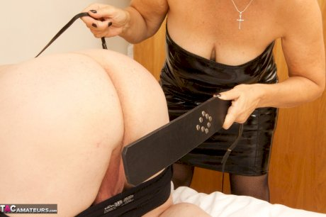 Mature woman in an assless latex dress paddles a man's ass before CBT session