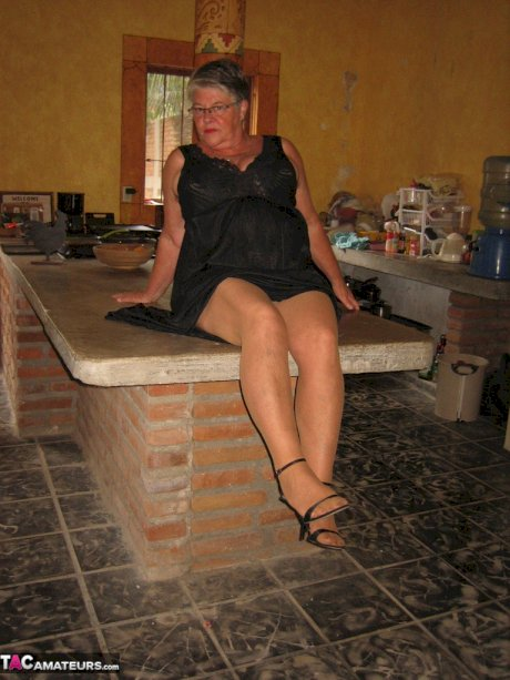 Fat oma Girdle Goddess strips to tan pantyhose on an island in the kitchen