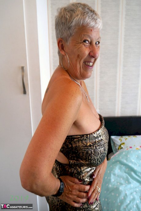Short haired granny Savana unleashes her large breasts while on her bed