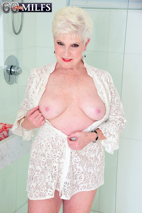 Hot blonde granny Jewel licks her red lips as she gets naked to shower