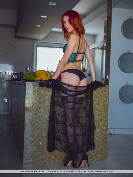 Natural redhead Elin Flame rocks her hot ass while getting naked in a kitchen
