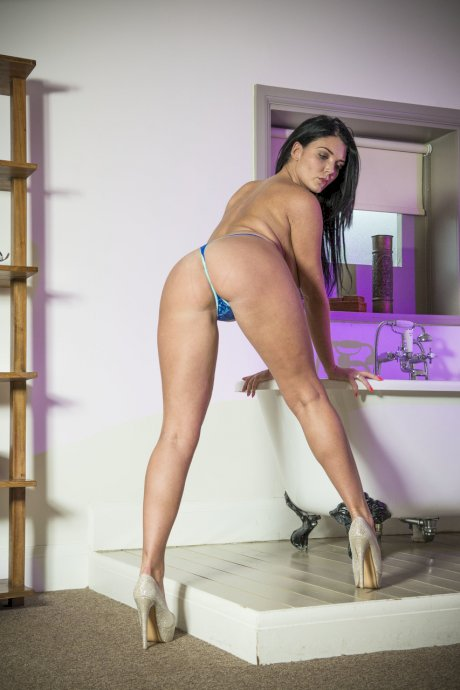 Brunette model Emma Leigh rocks her thong covered ass while freeing her boobs