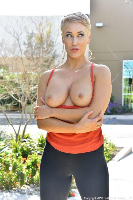 Amateur model with short hair shows off her natural tits on the sidewalk