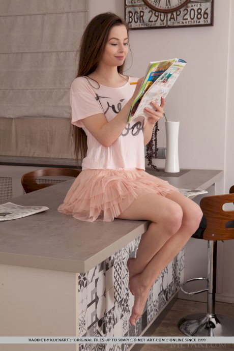 Sweet teen Haddie works on a crossword puzzle before posing nude in a kitchen