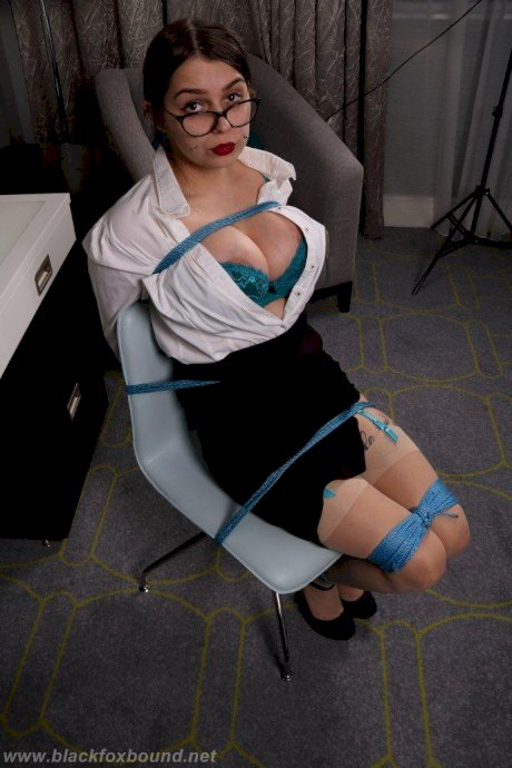 Fully clothed secretary exhibits healthy cleavage while bound and gagged