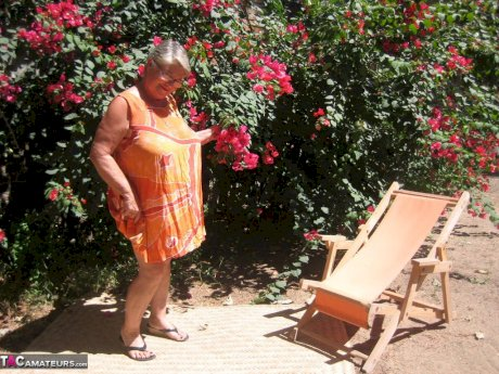Obese granny Girdle Goddess strips to her sandals on garden patio