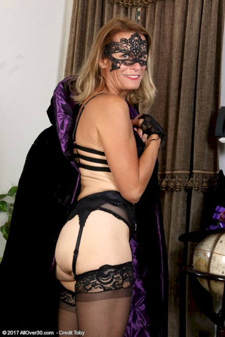 Aged blonde lady Jade Allan doffs a witch's outfit and mask in black stockings