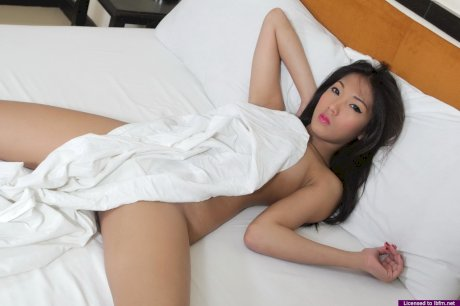 Young Asian girl Tee gets totally naked for the first time upon a bed