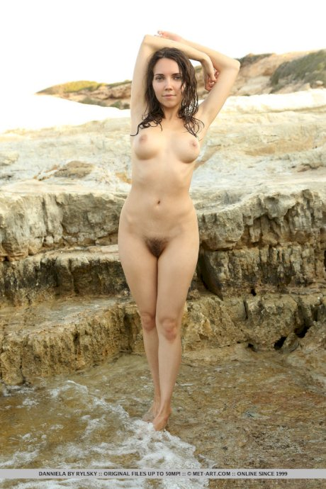 Teen solo girl Danniela frees nice tits from wet clothing on a sea shelf