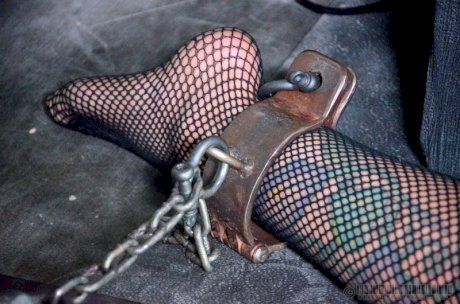 Restrained female Rain Degrey is locked away in a cage after extreme BDSM sex