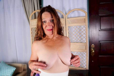 Nude granny model bares her saggy breasts as she goes about her business