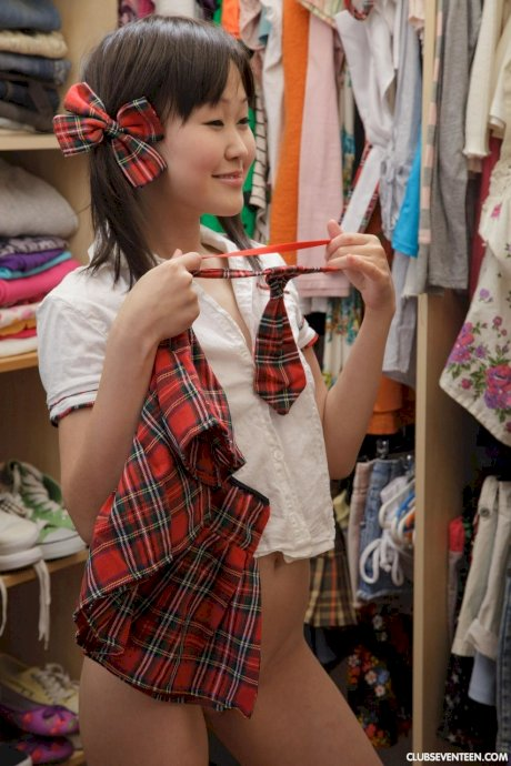Tiny Asian doll puts on school uniform and starts playing with toy afterward
