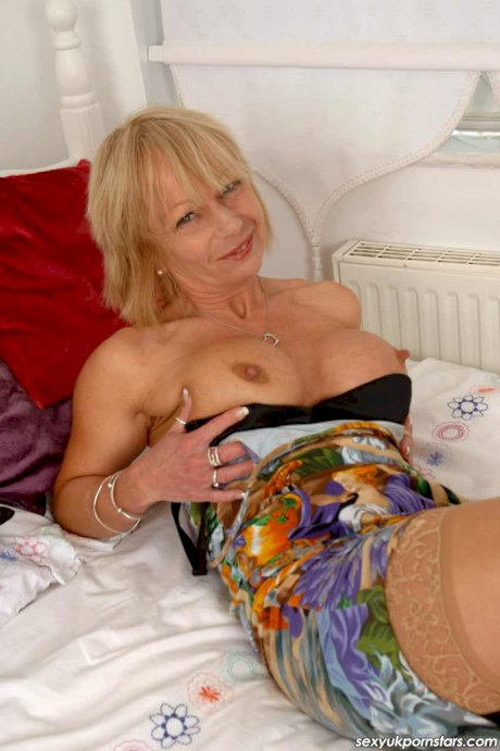 Sexy mature blond Jane Bond puts her pierced pussy on display in tan stockings