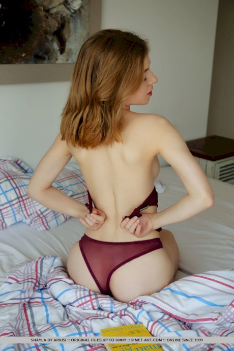 Young redhead Shayla doffs wine colored lingerie to get naked on her bed