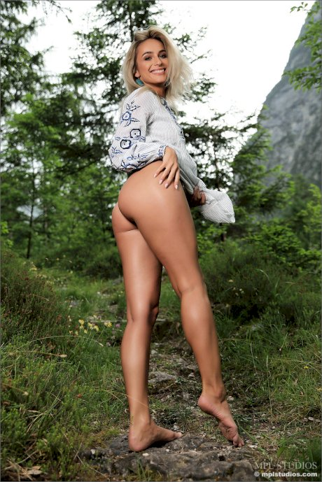 Blonde girl removes her dress to model totally naked in a forest setting