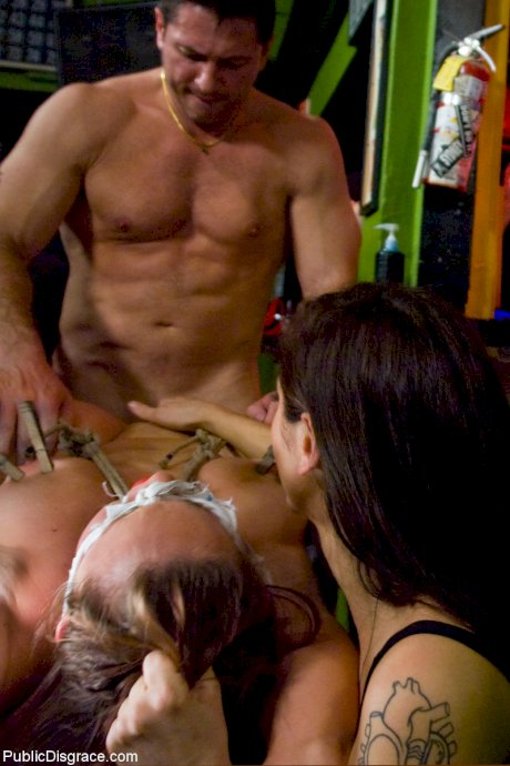 American babe Bella Rossi enjoys a bondage fuck in front of bar guests