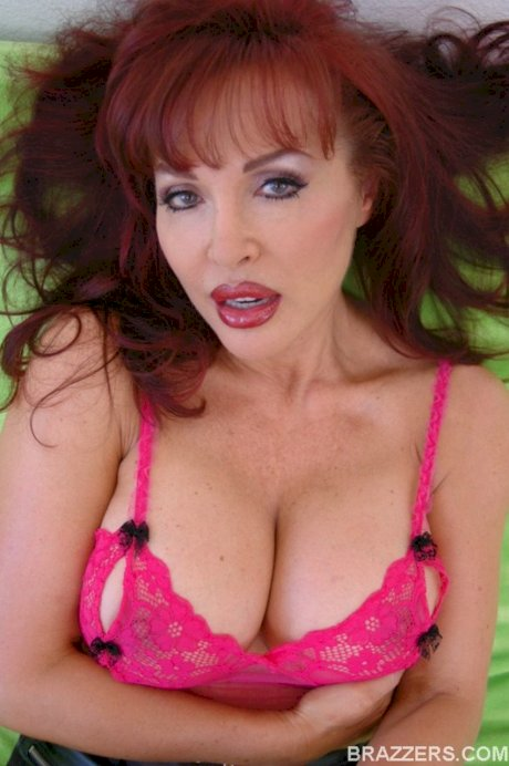 Busty redhead Sexy Vanessa shows & licks her breasts while wearing stockings