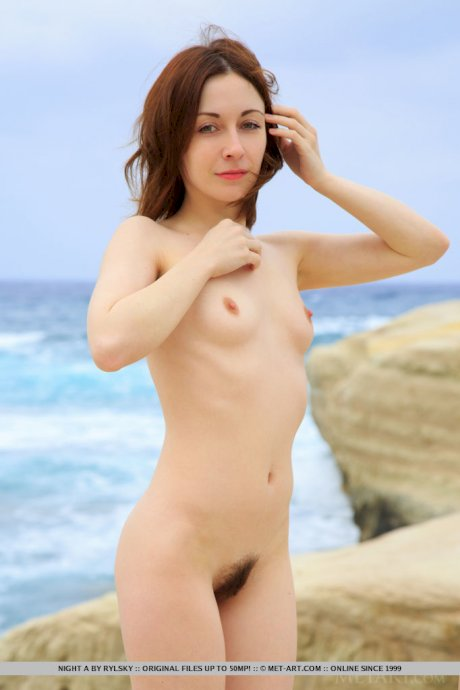 Petite redhead Night A shows her bush while posing naked beside the ocean